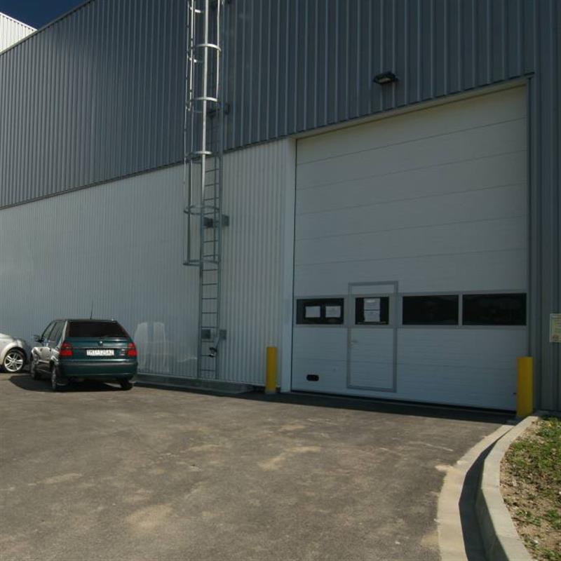 Průmyslová sekční vrata s dveřmi a pvc okénky
